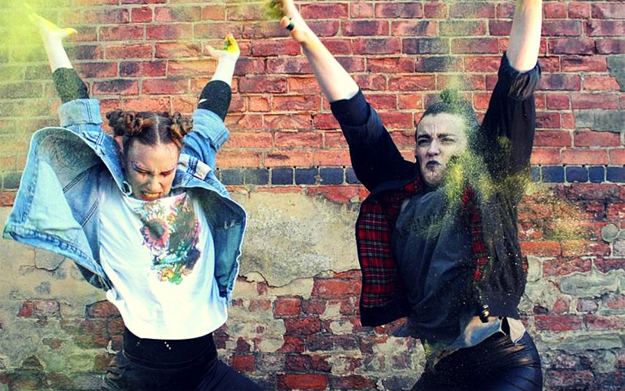 Two people jump in the air in front of a brick wall, showing yellow dust in the air around them