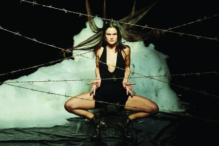 A woman crouches between a cloud and barbed wire