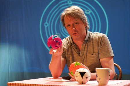 A man sets a table holding two ball-shaped toys, behind him on a blue curtain is an image of the solar system