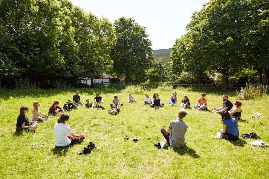 20 people sit cross-legged on the grass in a circle, surrounded by trees
