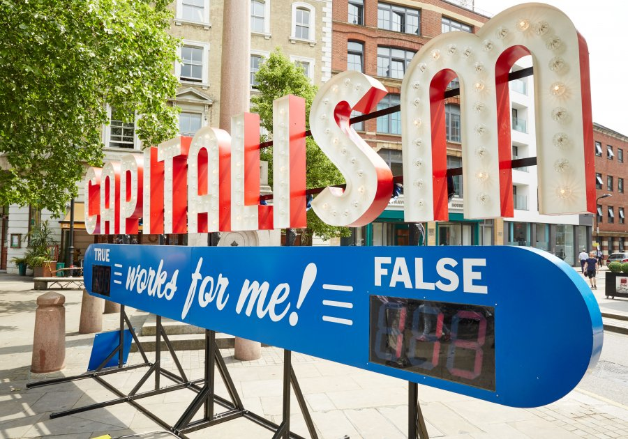 Large steel sign with 'Capitalism Works For Me!' on it and audiences need to decides whether that's true or false for them