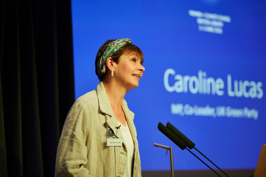UK Green Party MP and Co-Leader Caroline Lucas stands at a microphone in a lecture theatre