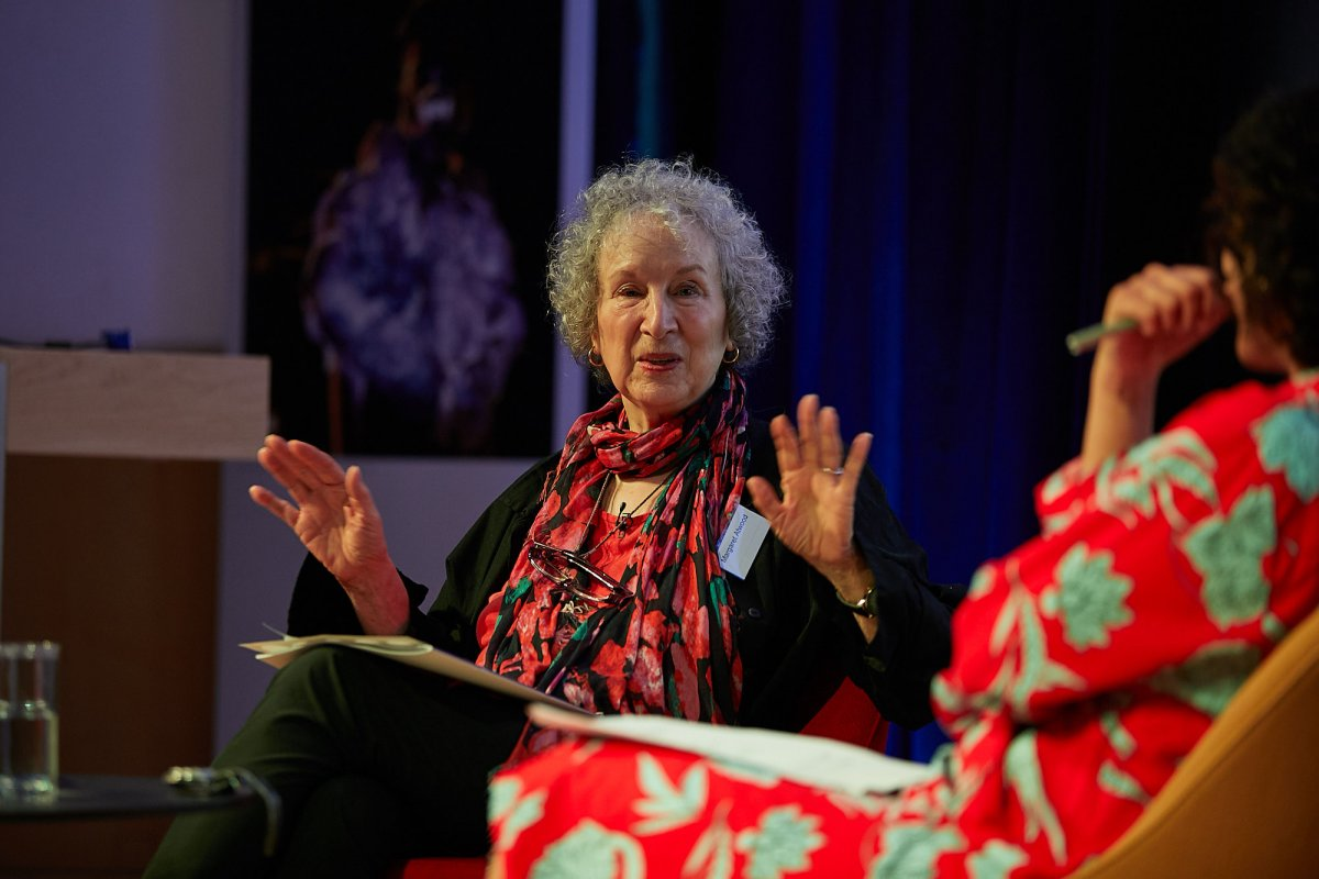 The author Margaret Atwood is seated, raising her hands in animated conversation with Samira Ahmed, seated partly out of frame to the right.