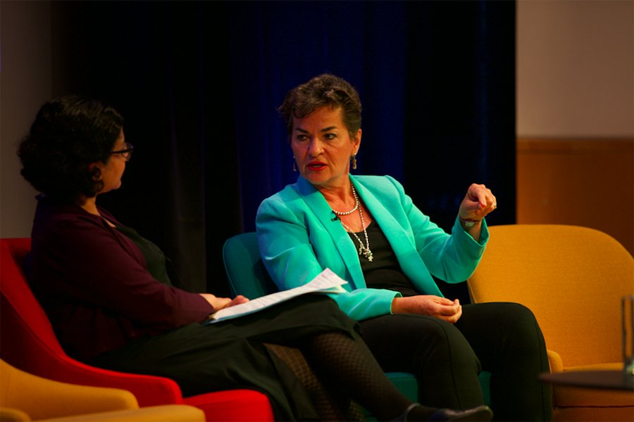 Christiana Figueres sits mid-frame, gesturing towards the floor, in conversation with Swaha Pattanaik, seated to the left.