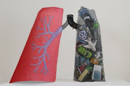 A sculpture of two lungs, one is red with blue capillaries, the other is made of mesh and contains small toys including cars and car symbols, an airplane and a pack of cigarettes