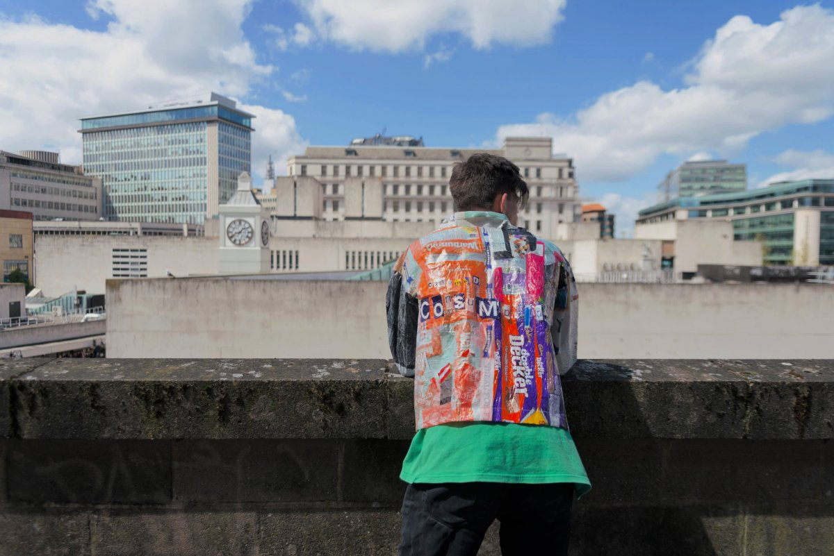 man in bright jacket stands overlooking river