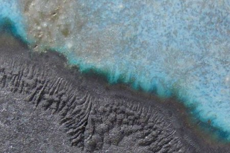 A very close up details of grey sand next to a blue rock