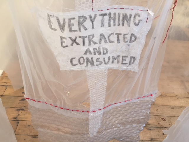 "A hanging translucent plastic curtain carries the text ""Everything Extracted and Consumed"""
