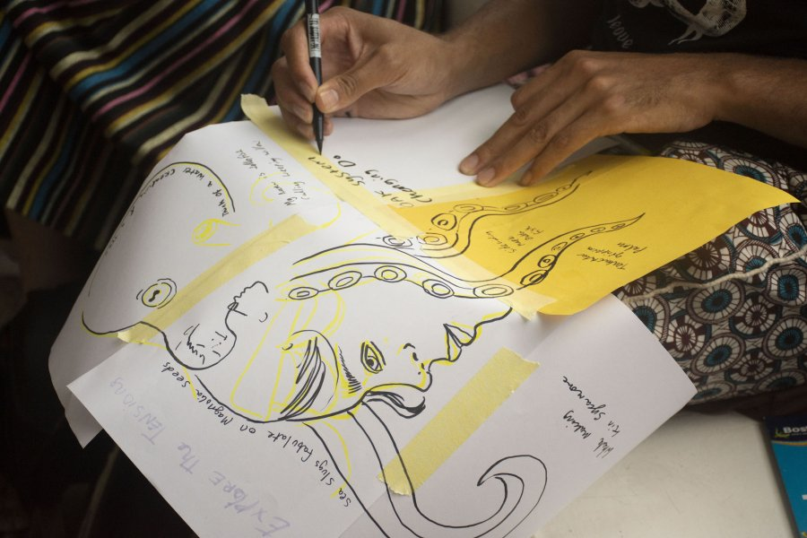 Several sheets of paper are held together by tape and covered in a large drawing of a face and tentacles and small excerpts of text. We see two hands as someone adds to the drawing