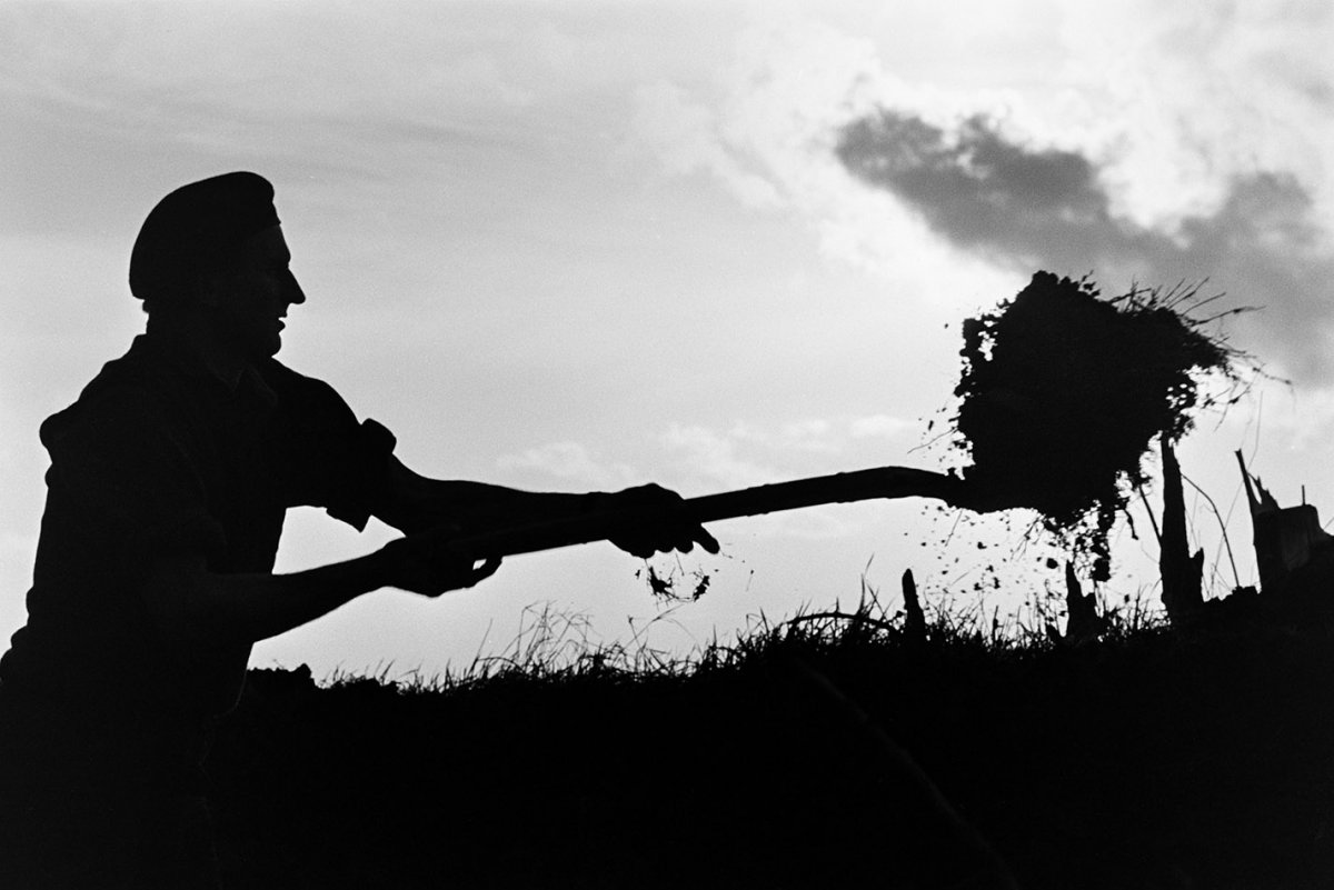 A silhouette, against a cloudy sky, of a male figure using a farming tool to dig soil