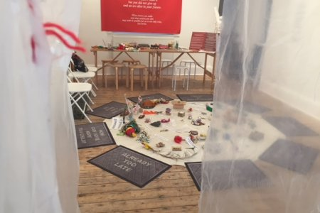A gallery space contains a white floor mat covered in objects and texts, surrounded by door mats with texts including 'Already Too Late' and 'How Can I Give Hope to a Child?'