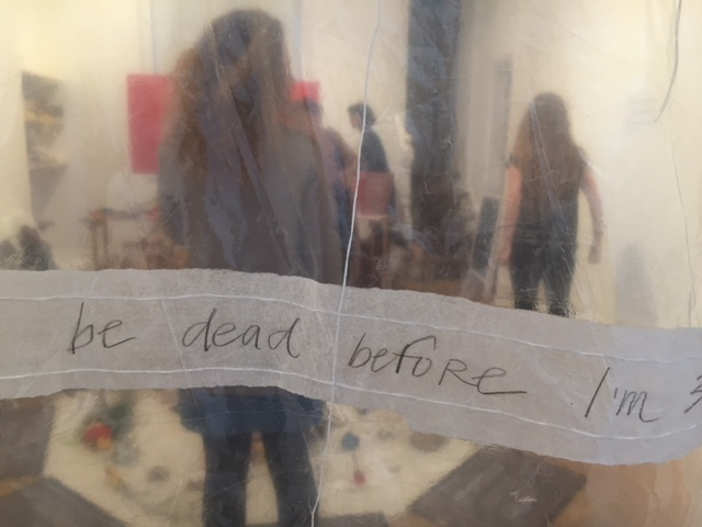 "We are looking through a plastic sheet carrying the words ""be dead before I'm"". Behind we can see several figures standing in a small white room and objects on the floor and walls."
