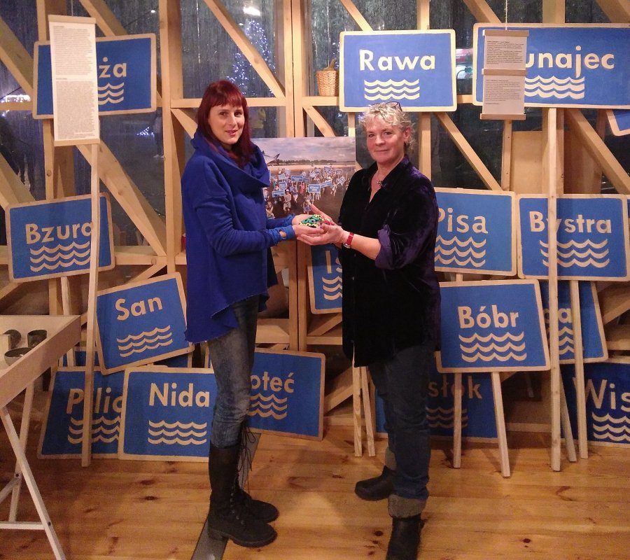 Two women exchanging a seed pouch surrounded by placards with place names on them
