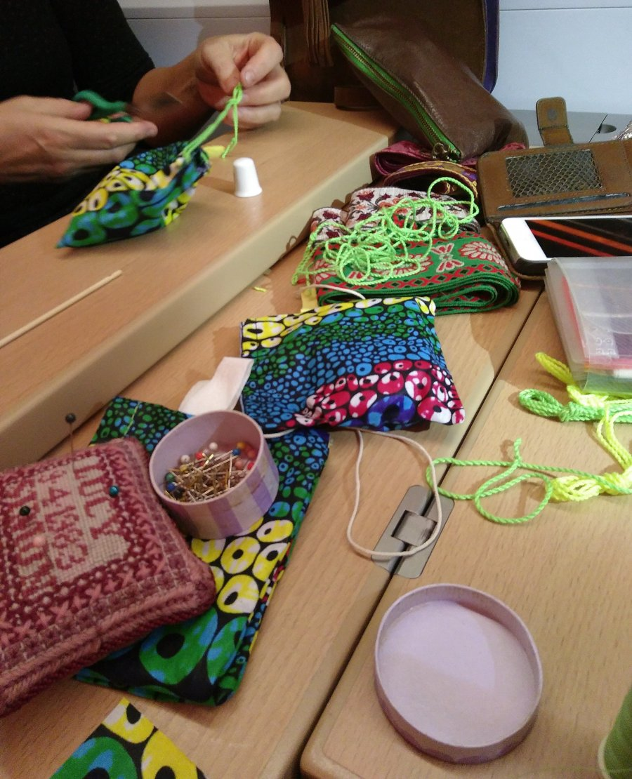 Pins, fabric, thread and hands sewings seed pouches on a train table