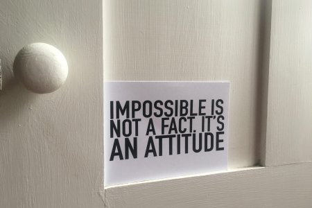 Door with handle and postcard resting on ledge with text on saying Impossible is not a fact, it's an attitude