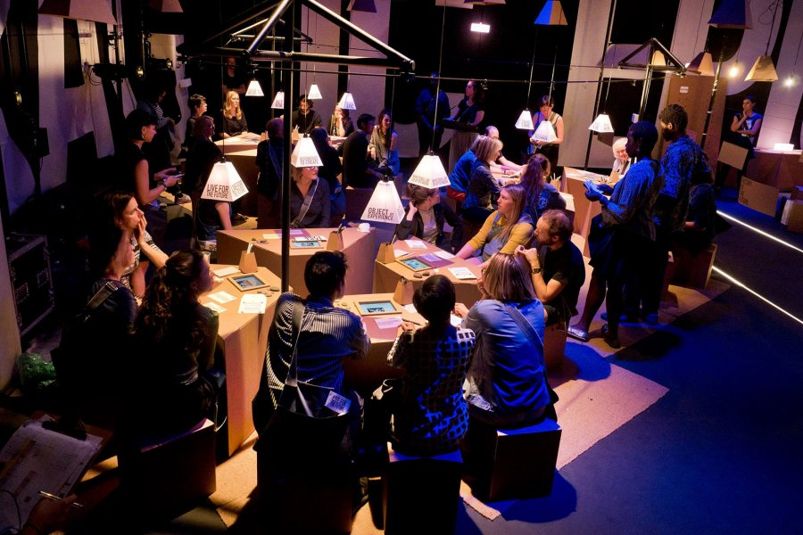 Audience members/participants in a performance gather around cardboard tables, with discussion points written on paper lamps above them.