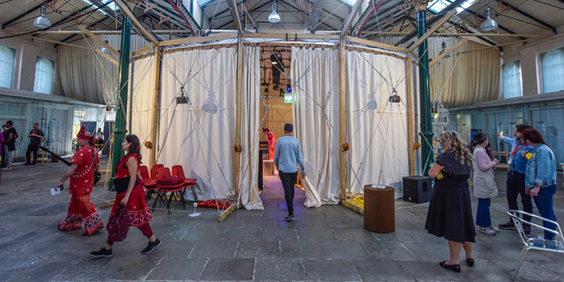 A performance space, made of a wooden frame and canvas drapes, stands in the middle of a civic hall. People walk by and enter the space, where a performance area is lit.