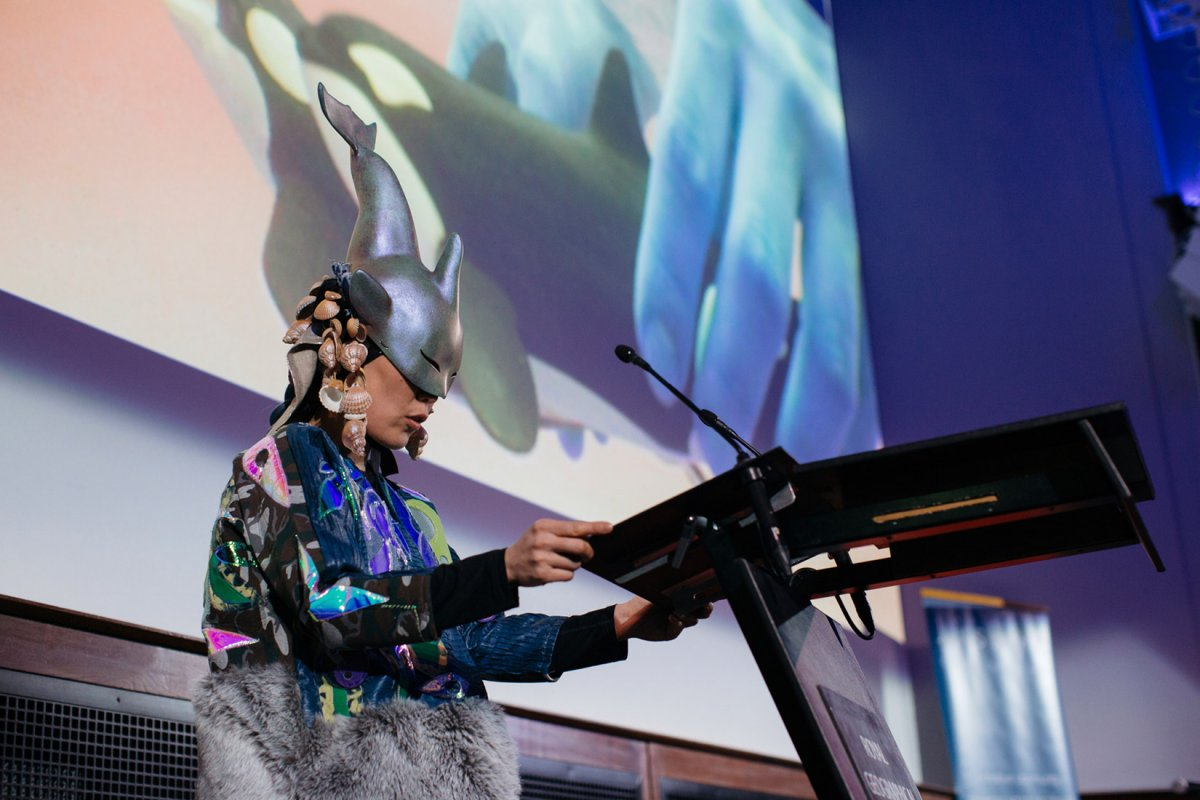 A performer stands at a podium wearing an orca-shaped headdress adorned with dangling shells. They are stood behind a projection showing two down-scaled orcas being held by blue, human hands.