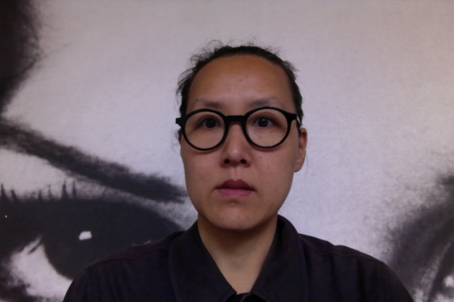 Artist Hwa Young Jung looks into the camera, wearing a black top and with black, thick-rimmed circular glasses.