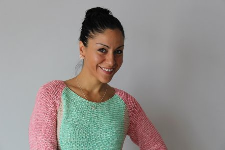 Rose poses in front of a white background, wearing a pale pink and green sweater.