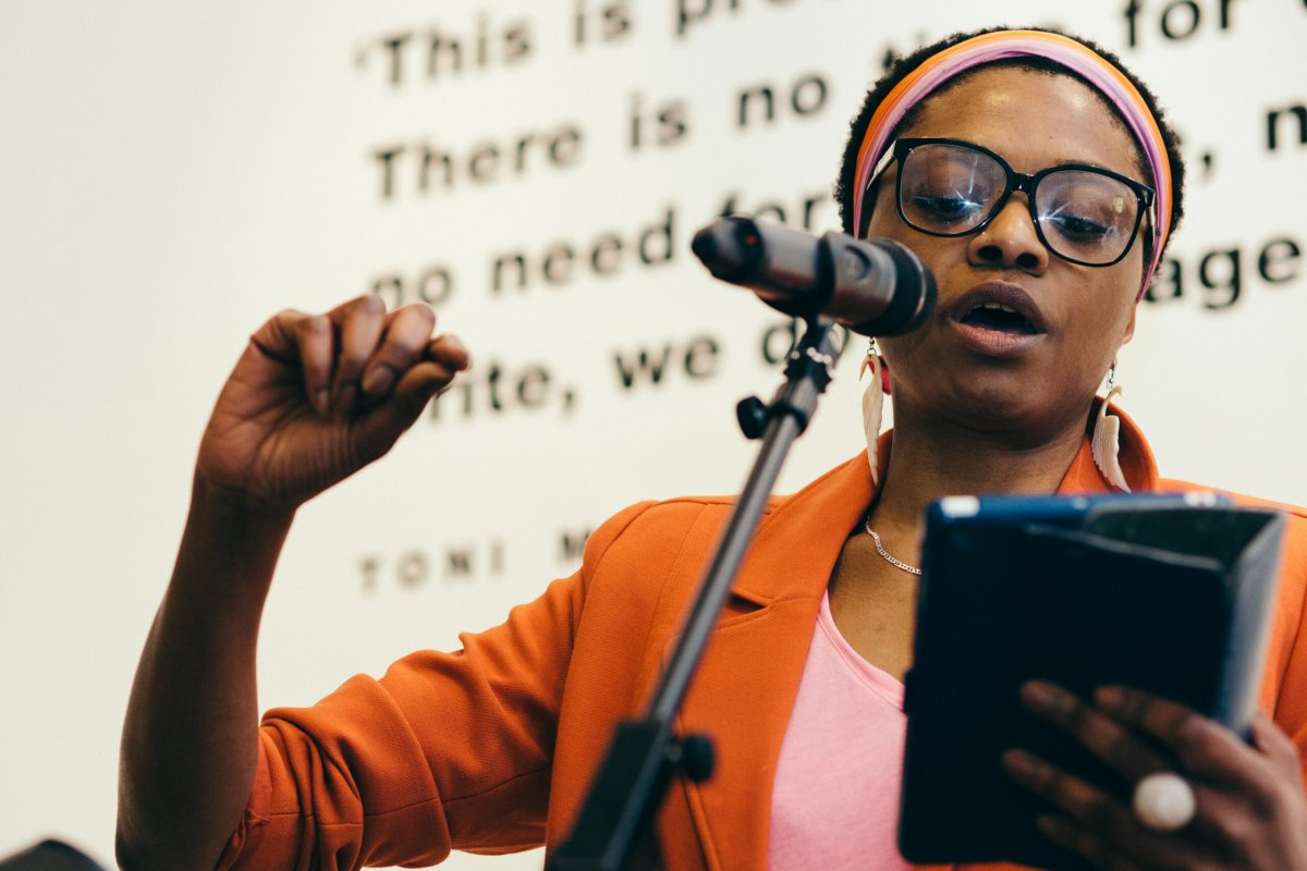 Zena Edwards, poet and performer, reads a text into a microphone.