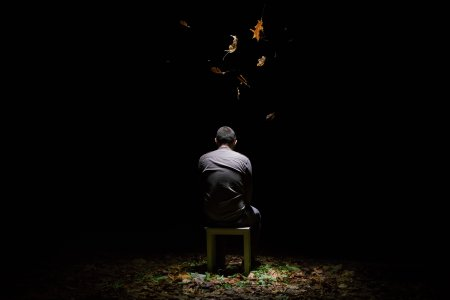 Person sitting in a dark space with a light from above illuminating leaves falling on them