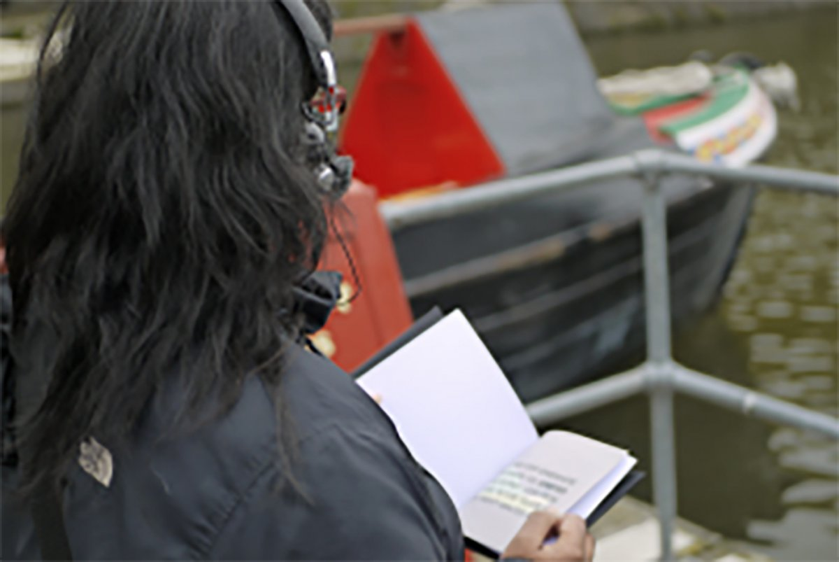 A person with shoulder length hair photographed from behind so face isn't visible is listening to the audio tour while reading a booklet