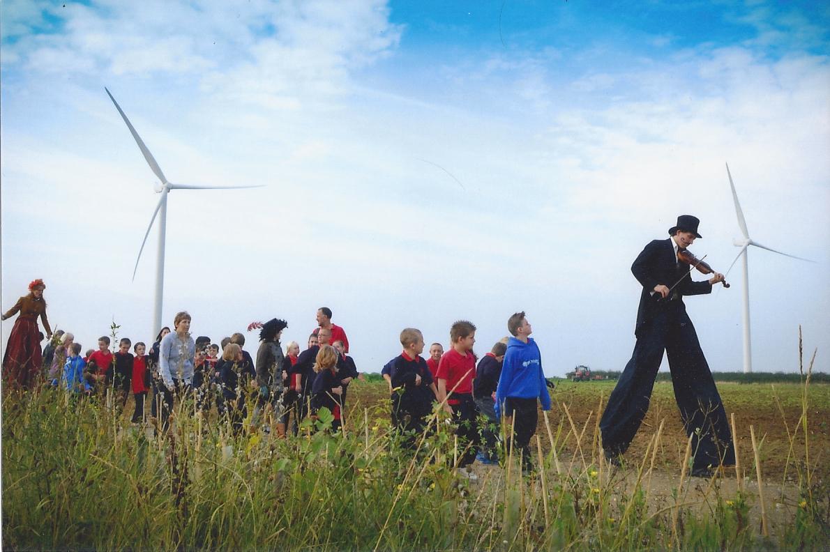 Stilt walkers and children walking through long grass at a wind farm